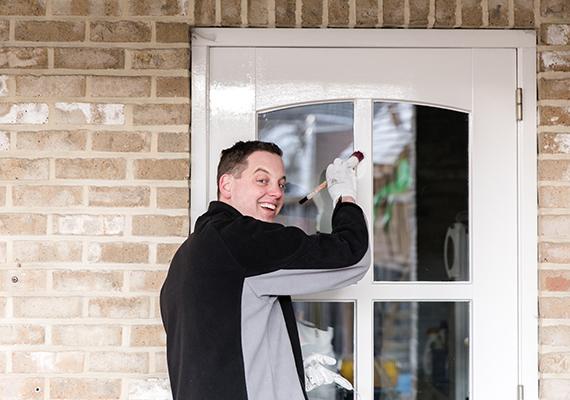 Schilder die bezig is met het onderhouden van een deur