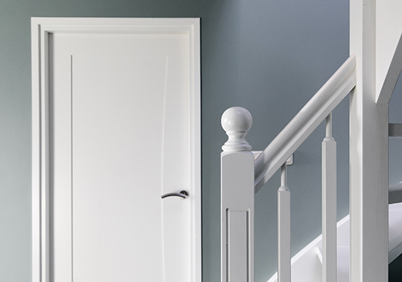 Mooi geschilderde trapleuning met een deur