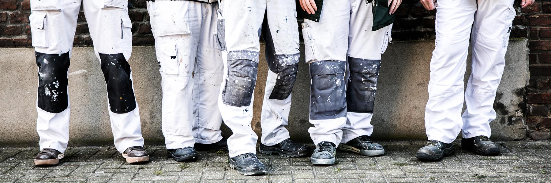 5 schilders die met hun gebruikte broeken op de foto staan